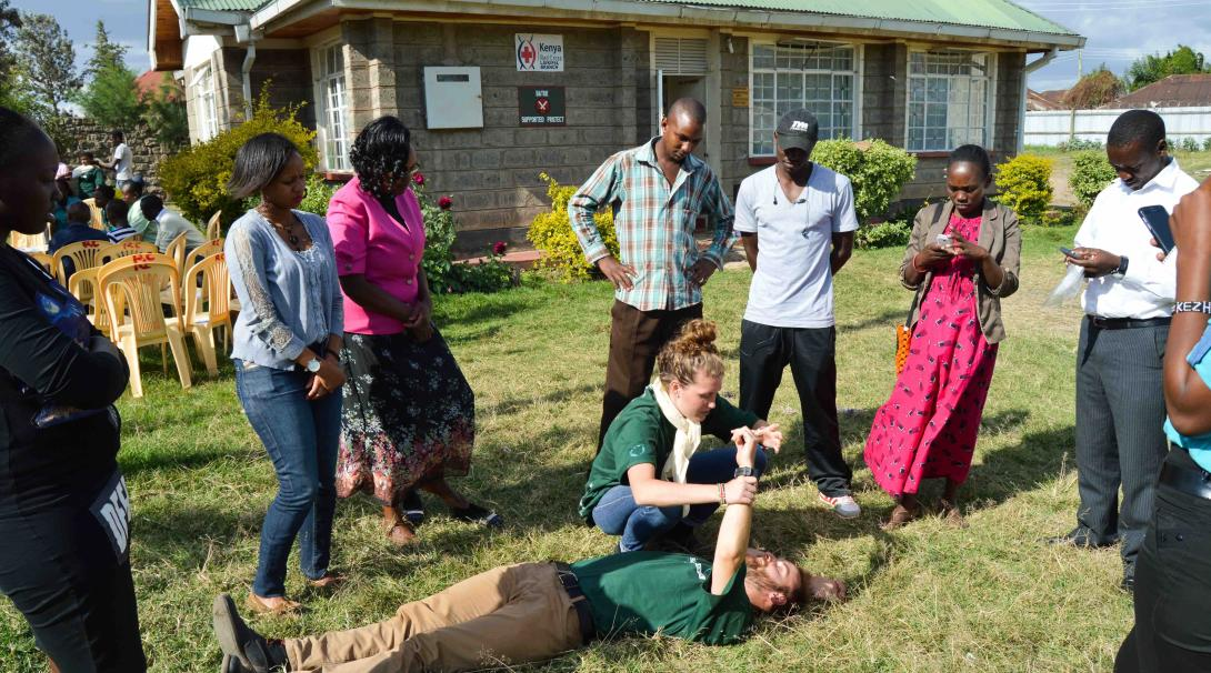 A couple of Projects Abroad medical volunteers teach some first aid techniques to local people in Kenya during a medical outreach.